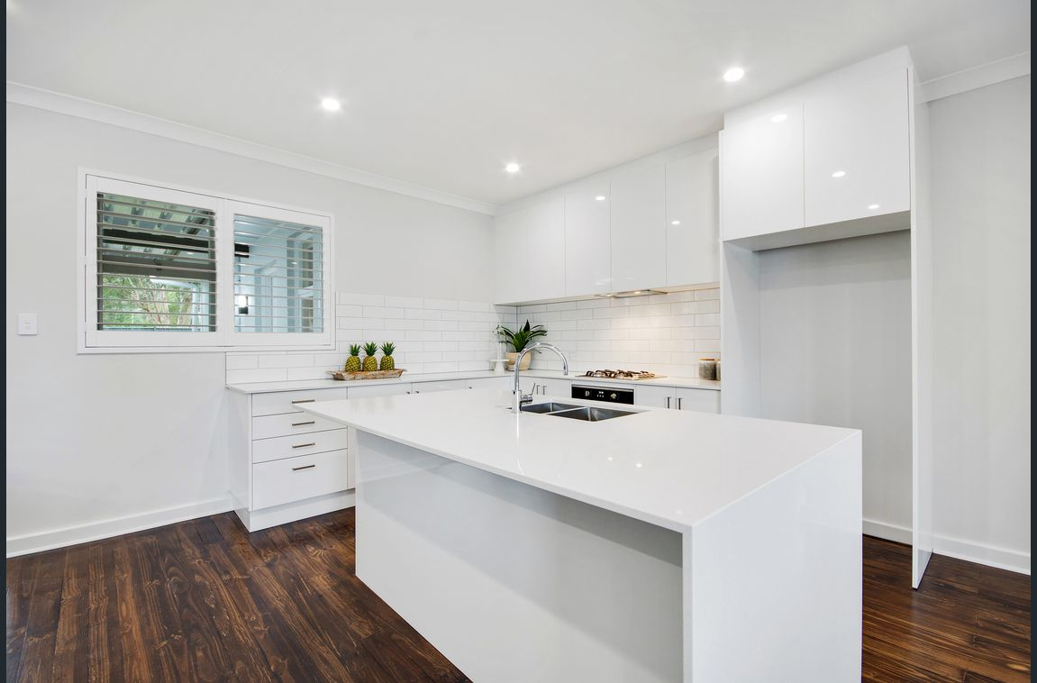 white kitchen island renovation with timber floors