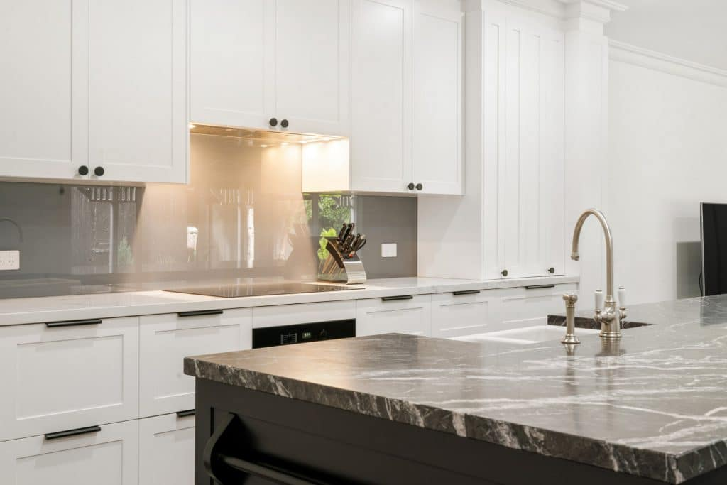 white cupboards with black marble kitchen renovation